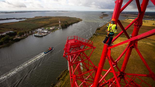Рабочий на 100-метровой высоте при монтаже фигурной опоры ЛЭП в Калининграде